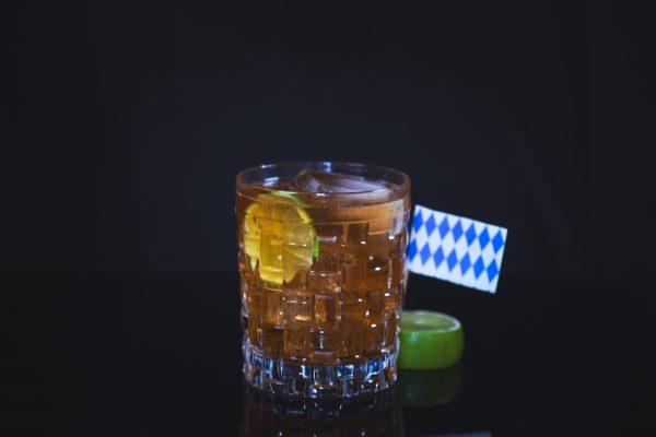 Rumliqueur und Ginger Ale in ein Glas geschenkt mit einem Bayern Fähnchen